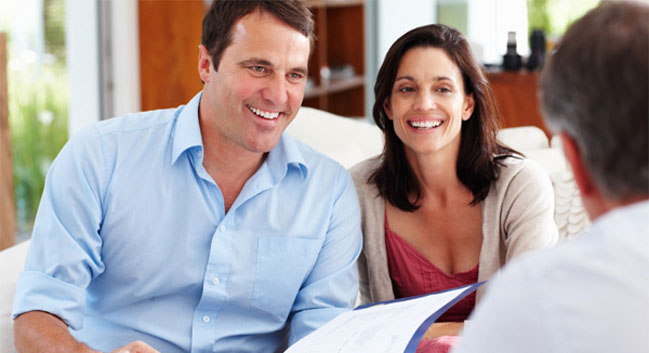 middle aged couple sitting with financial advisor