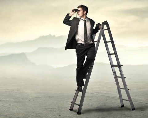 a financial advisor standing on a ladder looking through binoculars.