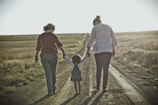 grandma, daughter, and granddaughter walk down the road together