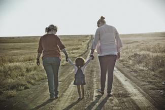 grandma, daughter, and granddaughter walk down the road together
