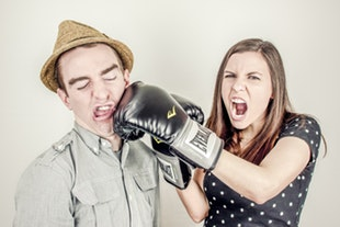 a woman wearing boxing gloves playfully punches her spouse in the face