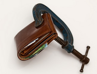 a wallet is stuck between a vice symbolizing debt pressures