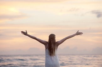 a woman looking out over the ocean with her arms outstretched in pure joy