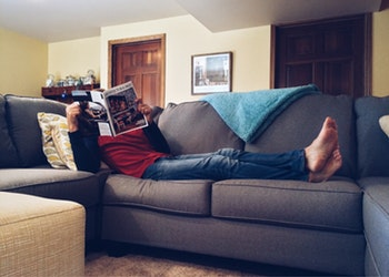 a man relaxes on his couch while reading a book
