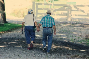 elderly couple walks together holding hands